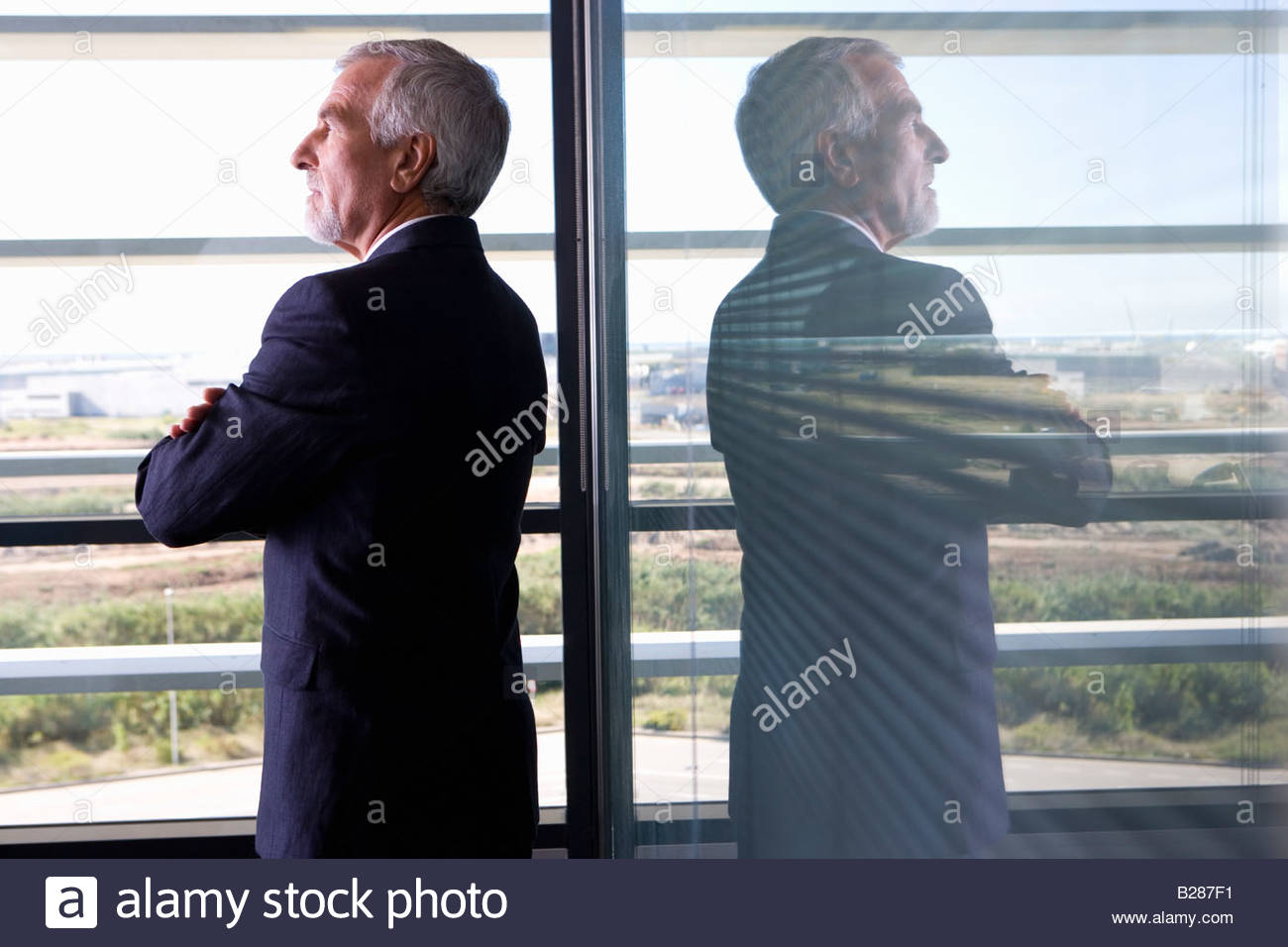 Businessman with arms crossed by window in office, rear view - Stock Image