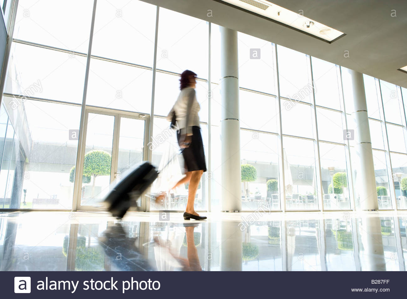 Businesswoman with luggage, low angle view (blurred motion) - Stock Image