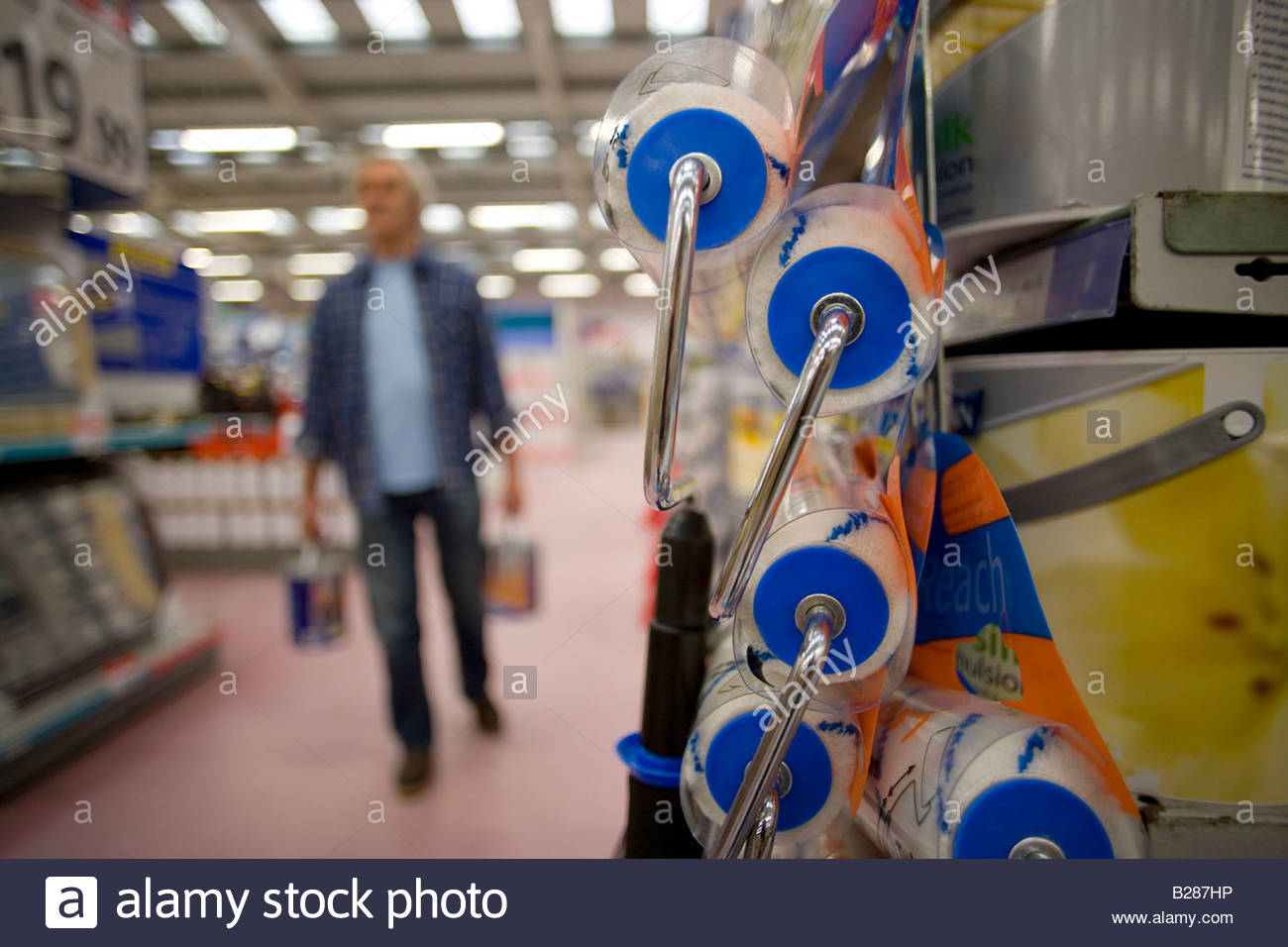 Man in hardware store, close-up of paint rollers - Stock Image