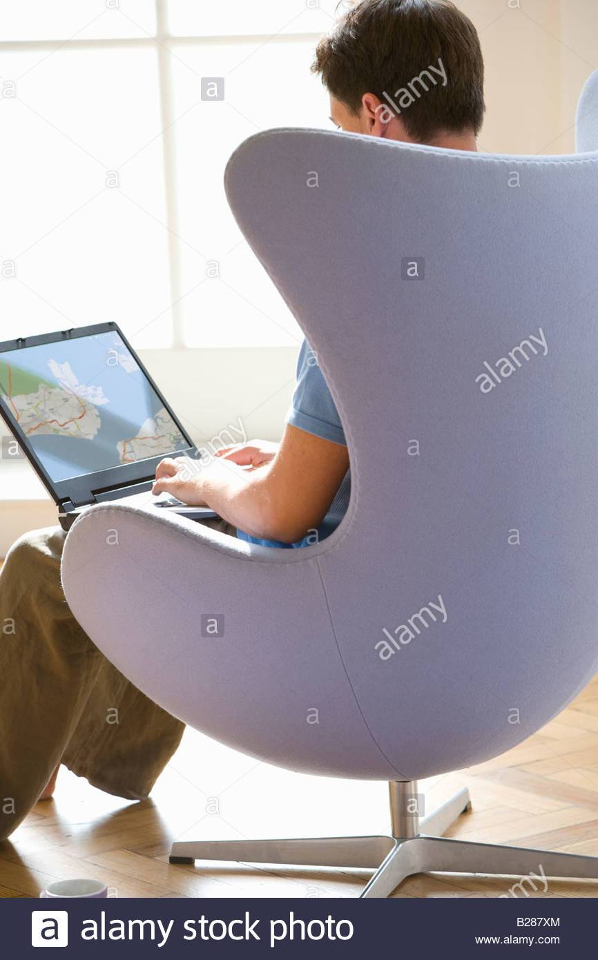 Man with laptop computer in armchair, rear view - Stock Image