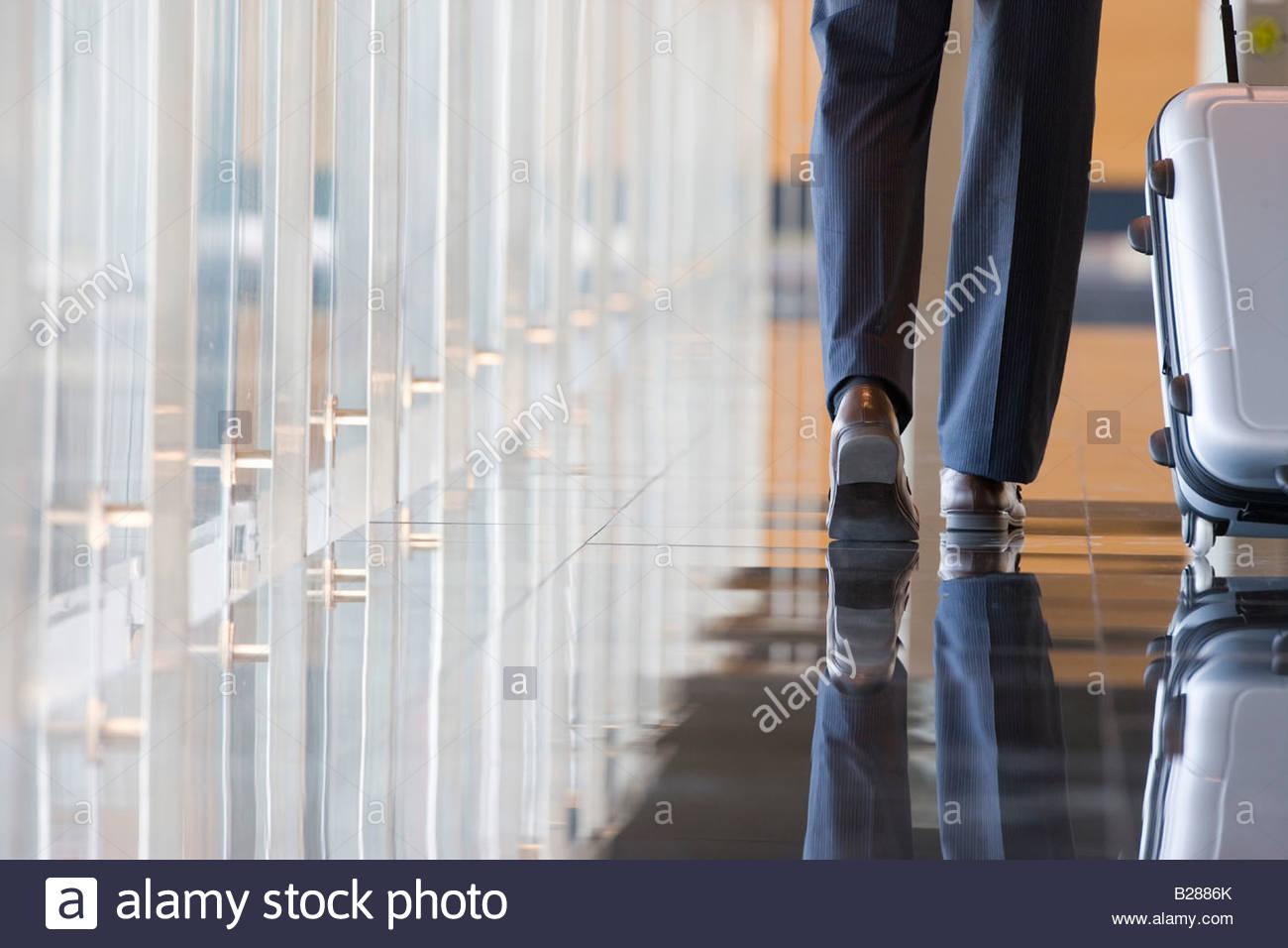 Businessman wheeling luggage in lobby - Stock Image