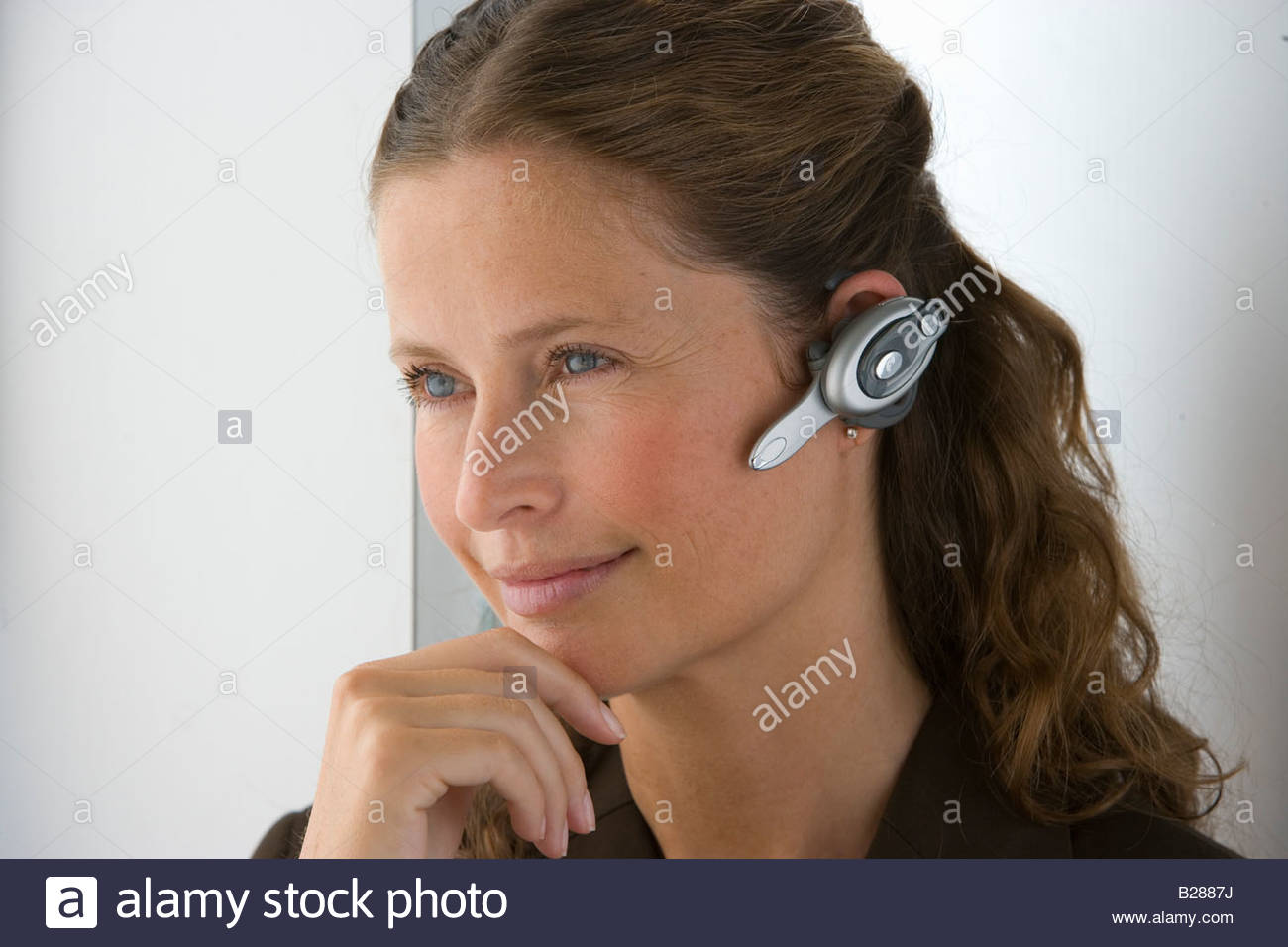 Businesswoman with hands-free cell phone headset Stock Photo