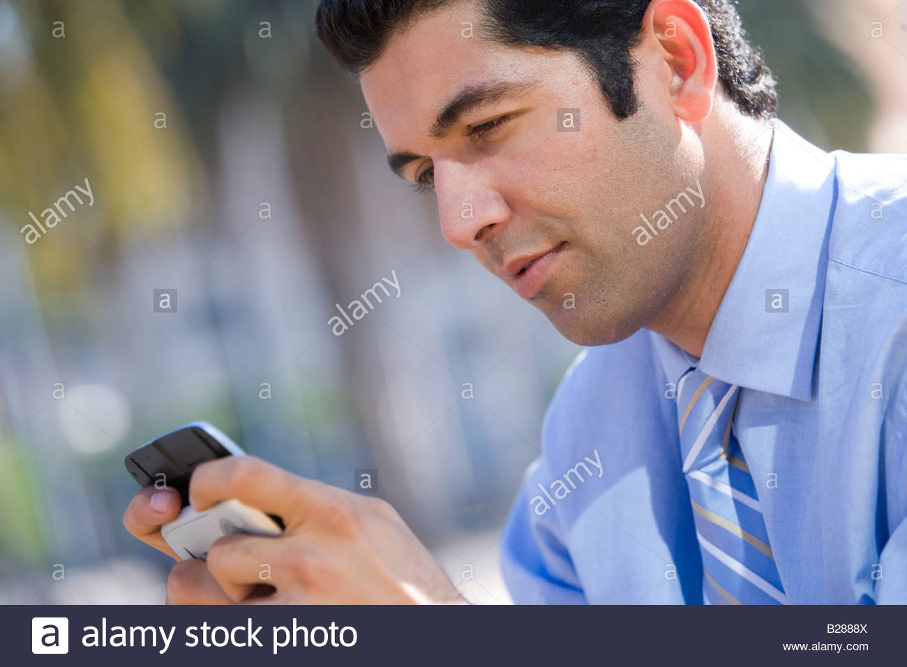 Businessman checking text messages on cell phone - Stock Image