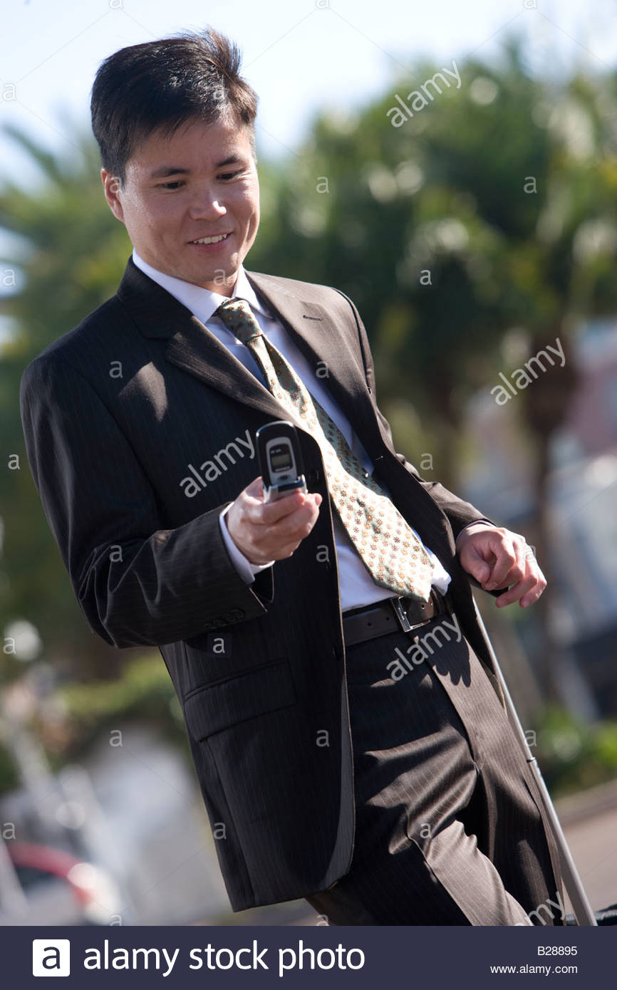 Businessman checking text messages outdoors - Stock Image