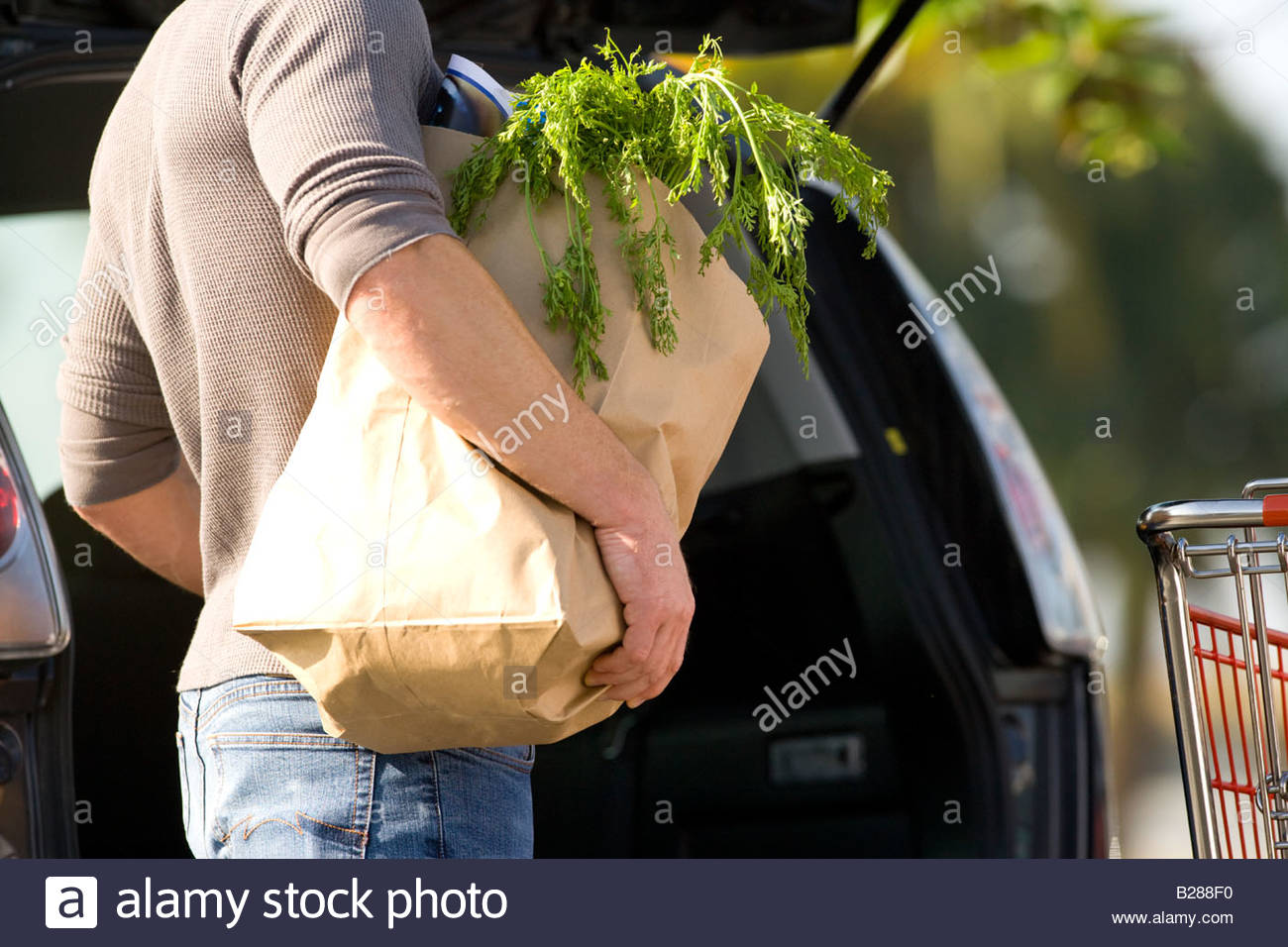 Man loading groceries into rear of car - Stock Image