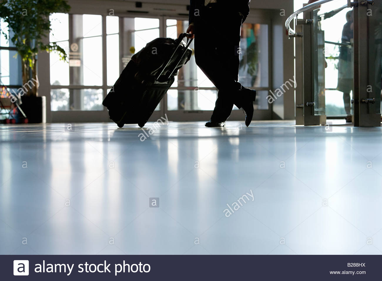 Businessman waiting with luggage in airport - Stock Image