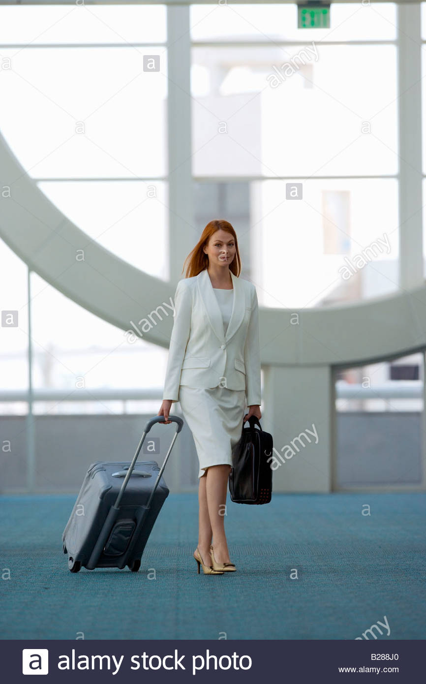 Businesswoman with rolling luggage in airport terminal - Stock Image