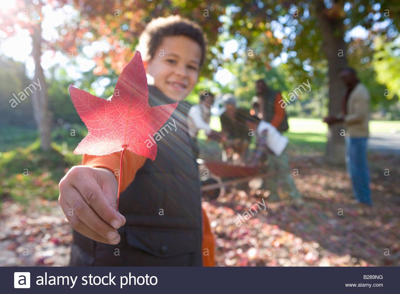 Multi-generational family doing yard work in autumn - Stock Image