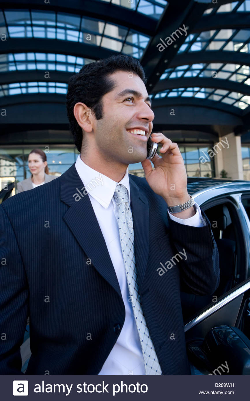 Businessman talking on cell phone in urban setting - Stock Image