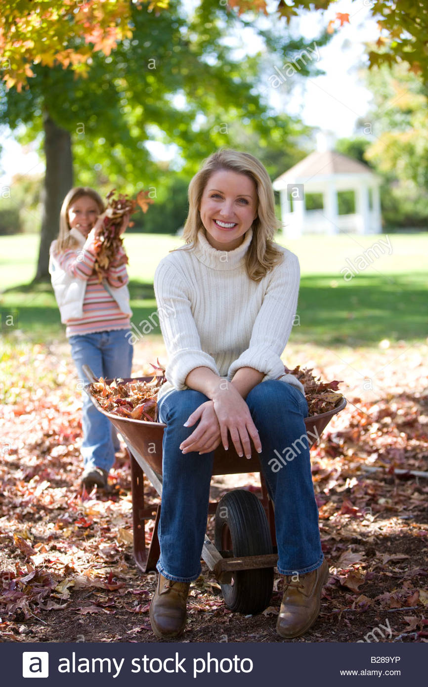 Mother and daughter doing yard work in autumn - Stock Image