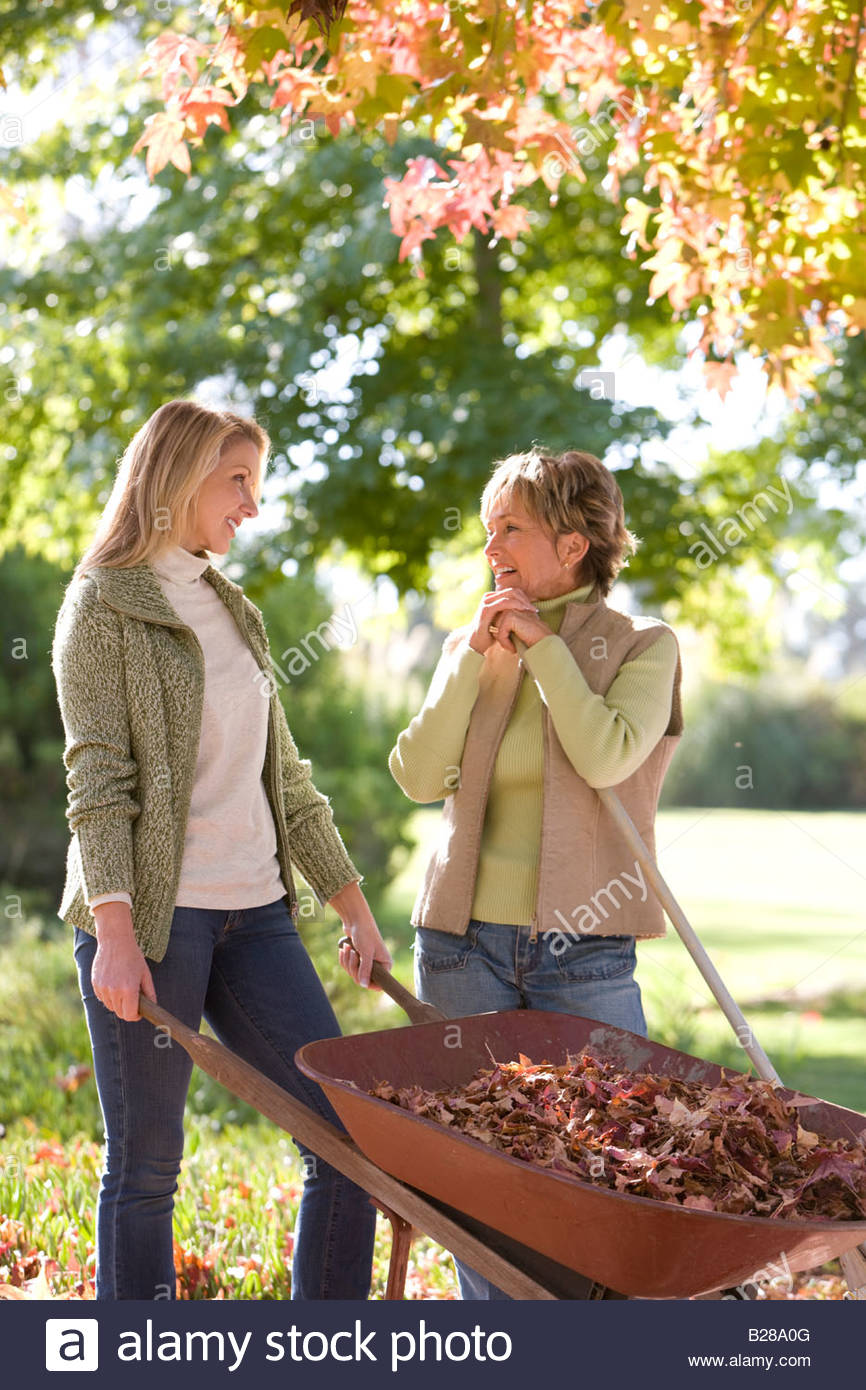 Women doing yard work in autumn - Stock Image