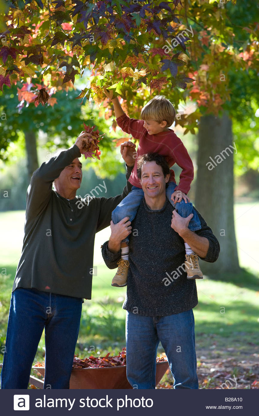 Multi-generational family doing yard work in autumn - Stock Image