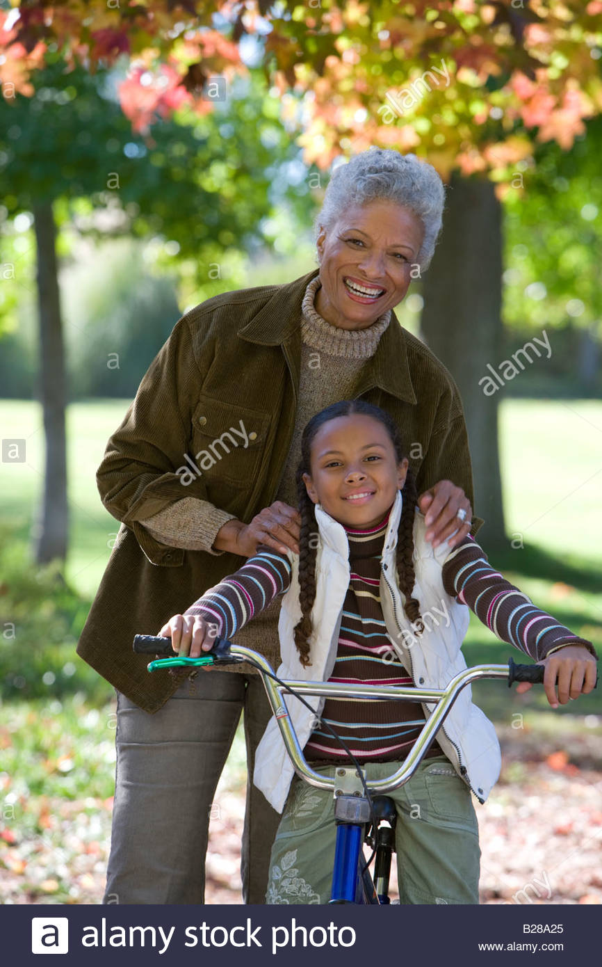 Grandmother helping granddaughter learn to ride a bicycle - Stock Image