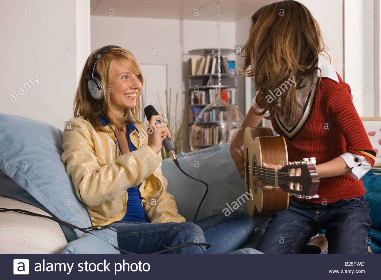 Two teenage girls making music - Stock Image