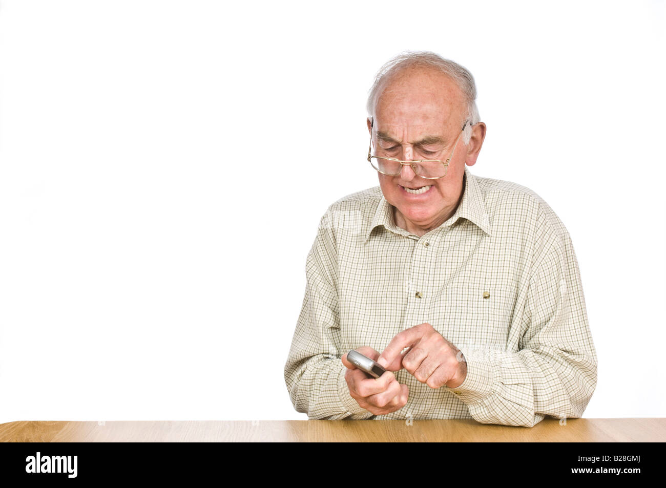 An elderly man getting frustrated trying to text or use the mobile phone with the small buttons and numbers. - Stock Image