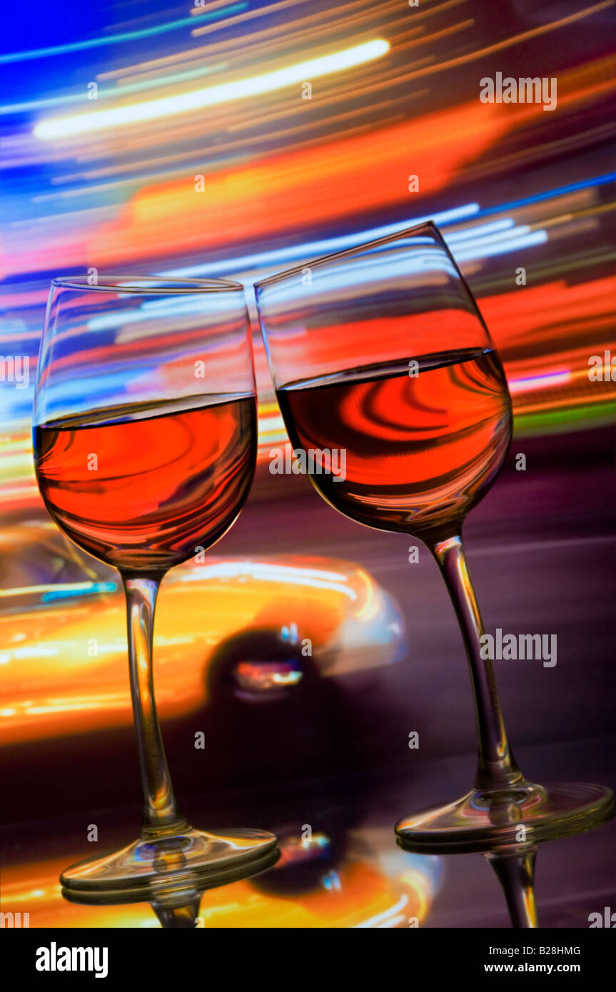 Two wine glasses lean together with blurred yellow taxi cab and streaks of neon lighting behind. Times Square New - Stock Image