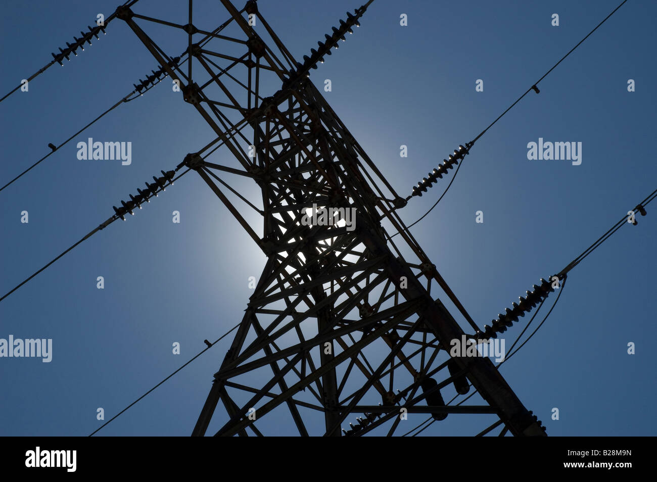 Electricity pylon (or tower) is back-lit by the sun over a blue sky. - Stock Image