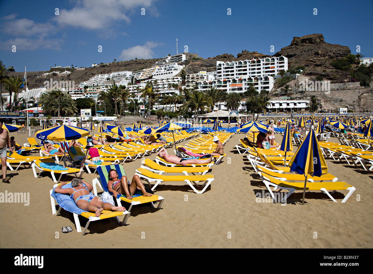 People on beach loungers with holiday resort apartments on hill Puerto Rico Gran Canaria Spain - Stock Image