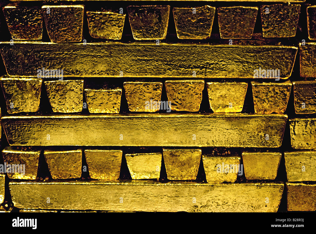 Traditionally shaped pure raw gold bars stacked in a secure bullion room safe - Stock Image