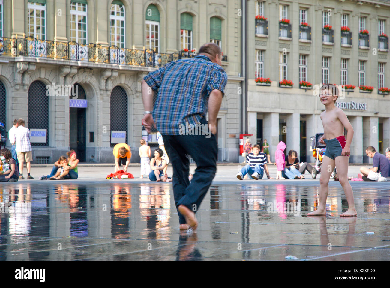 Father and son playing in the fountain in front of the House of Parliament, Bern, Switzerland. - Stock Image