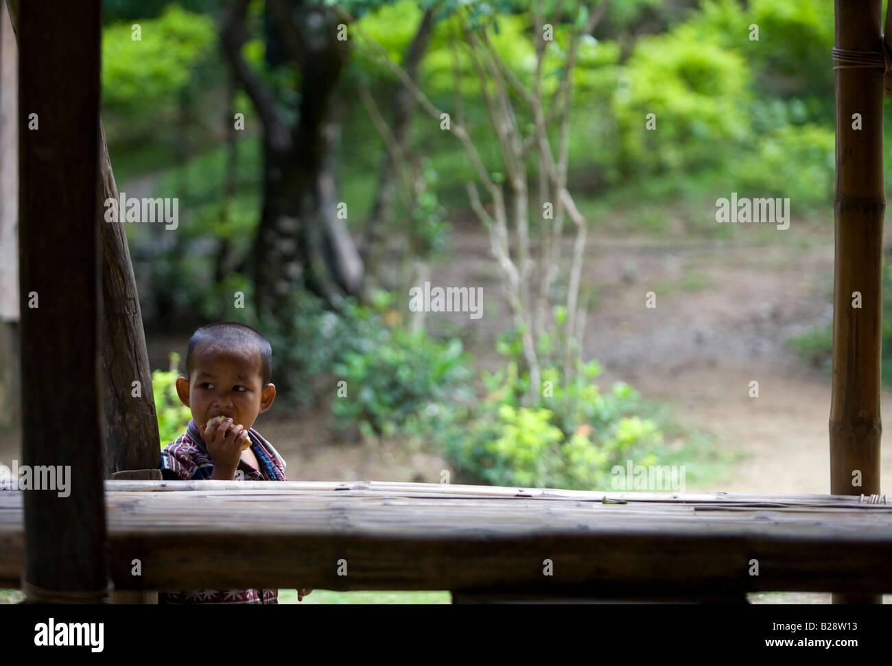 A Mangyan child eats a mango in the Panaytayan community near Mansalay, Oriental Mindoro, Philippines. - Stock Image