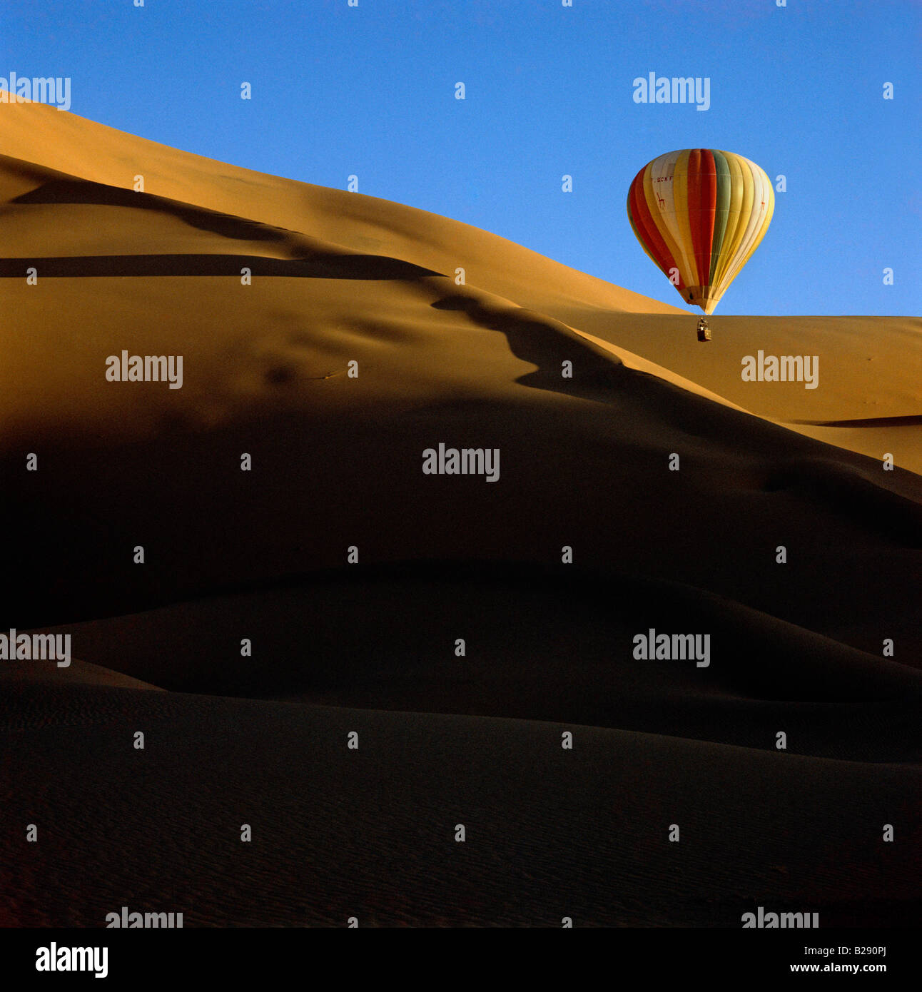 Balloon flying over desert in front of very high sand dune at sunset Erg Mehedjibat Algeria Sahara - Stock Image