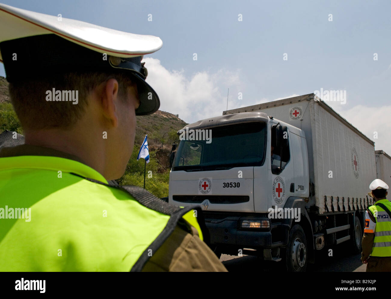 Military police watch red cross truck pass the Israeli border with Lebanon in Rosh Hanikra Israel - Stock Image