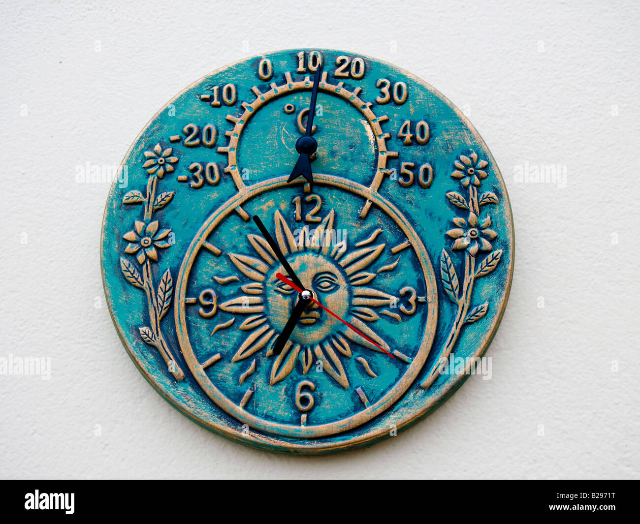 Ceramic clock and thermometer mounted on outdoor wall Stock Photo