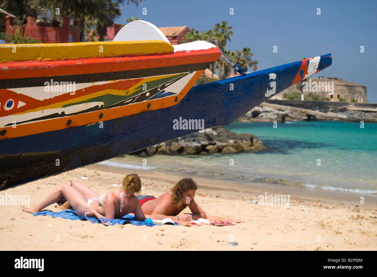 Sunbathers beside a pirogue boat Date 20 02 2008 Ref ZB583 110492 0031 COMPULSORY CREDIT World Pictures Photoshot - Stock Image
