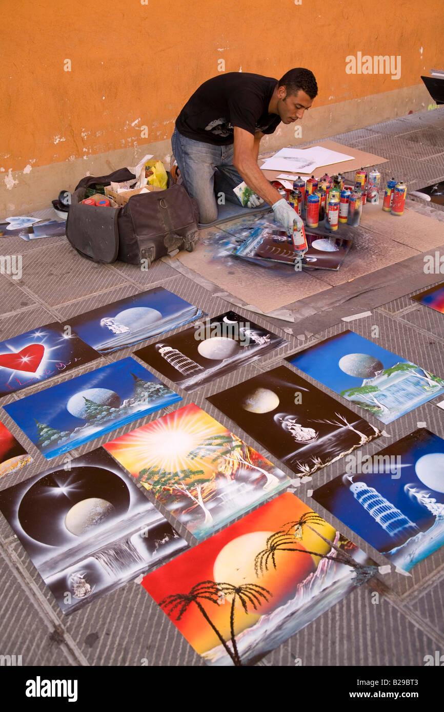 Street artist selling colourful images Pisa Tuscany Italy Europe - Stock Image