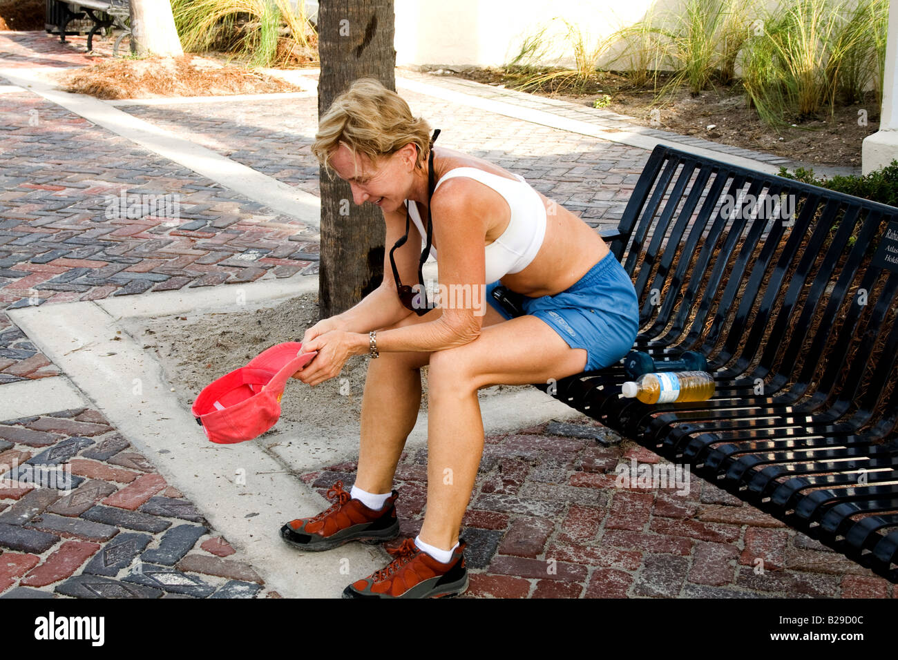 Middle-aged woman athlete resting with hat in hand on a bench in Atlantic Beach, Florida - Stock Image
