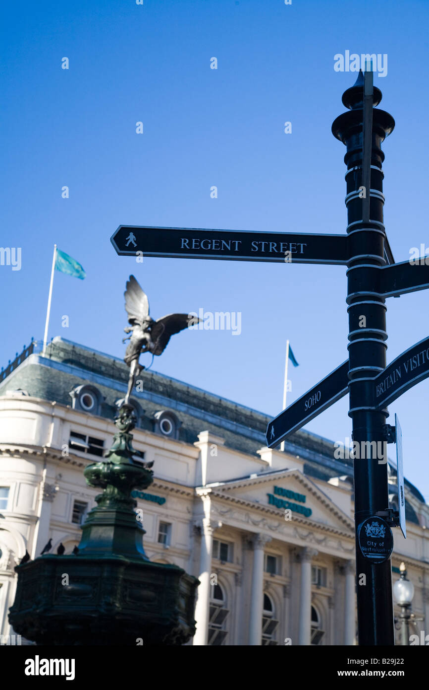 Tourist sign post in Piccadilly Circus with the statue of Eros and the Trocadero in the background - Stock Image