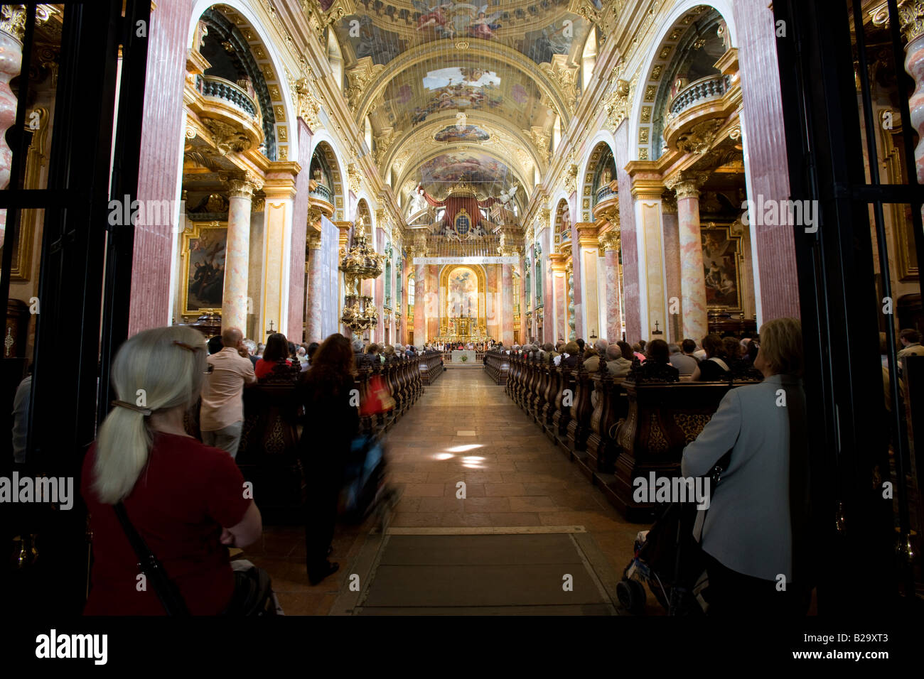 Congregation inside the 17thC Jesuit Church Vienna Austria.  Also known as the Church of the Franciscan Order - Stock Image