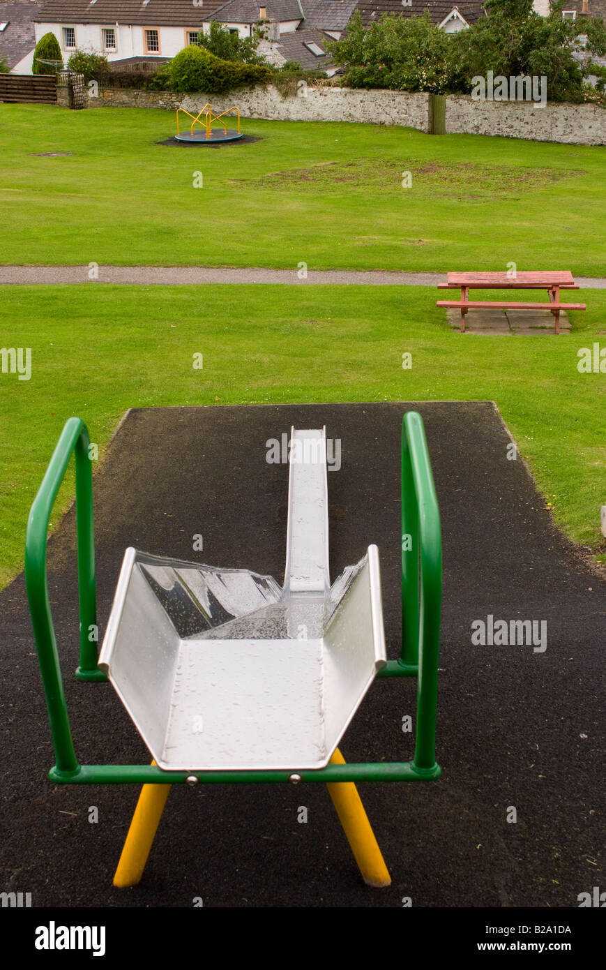 View Down a Childrens Slide with Empty Roundabout and Bench Seat in Playground Park at Kikcudbright Scotland United Stock Photo
