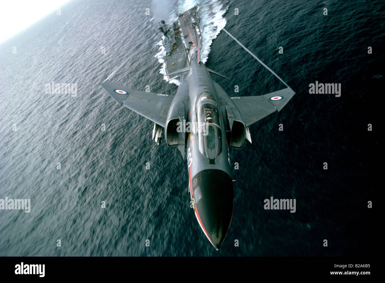 Phantom F4 jet aircraft with aircraft carrier in background - Stock Image