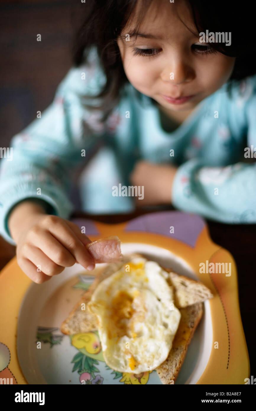 Girl aged five eats fried breakfast - Stock Image