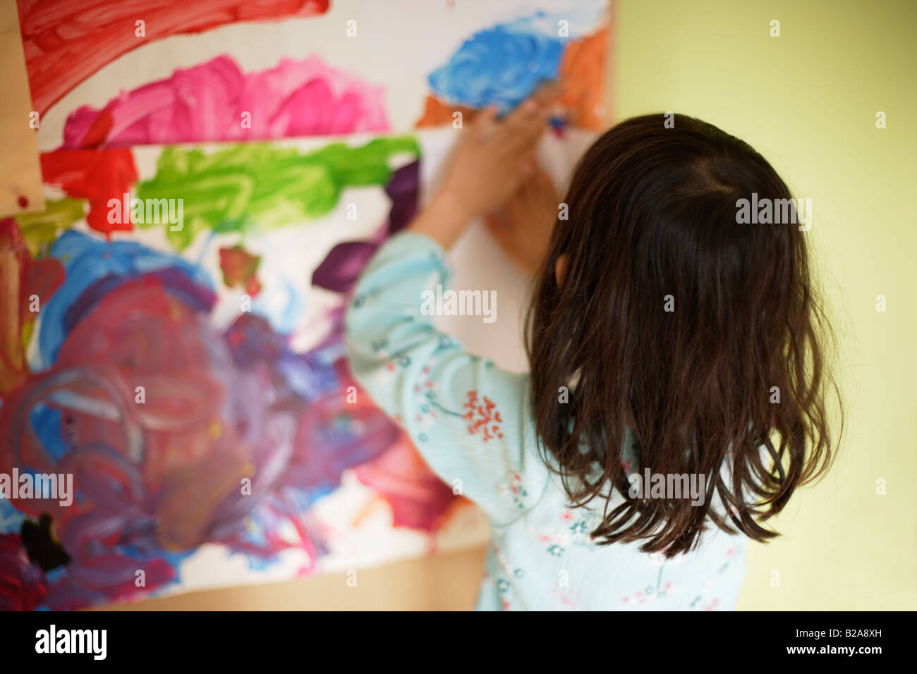 Five year old girl sticks artwork on her bedroom pinboard Mixed race indian ethnic - Stock Image