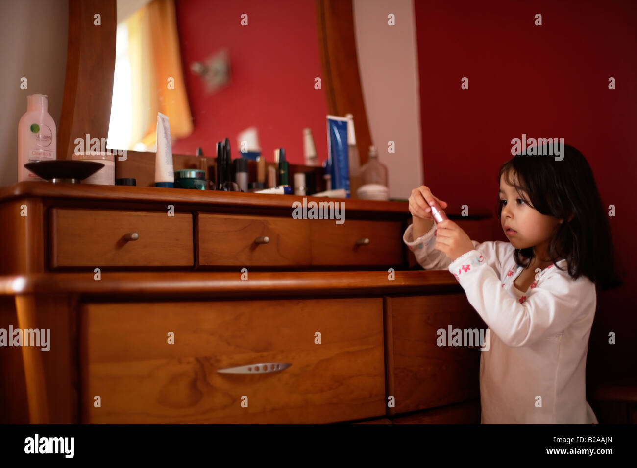 Five year old girl sneaks a look at her mother s lipgloss Mixed race indian ethnic and caucasian - Stock Image