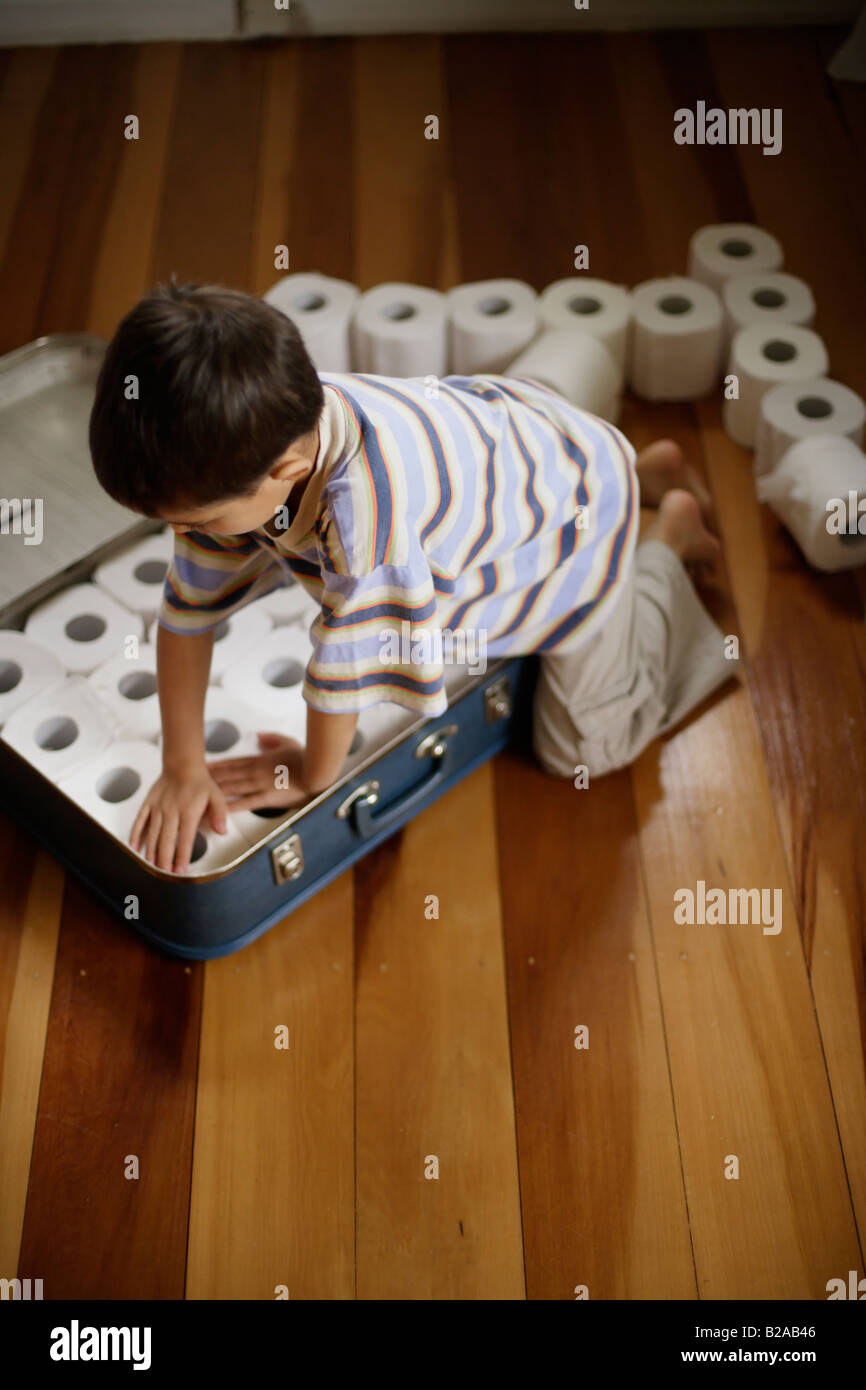 Six year old boy packs toilet rolls into suitcase Mixed race indian ethnic and caucasian - Stock Image