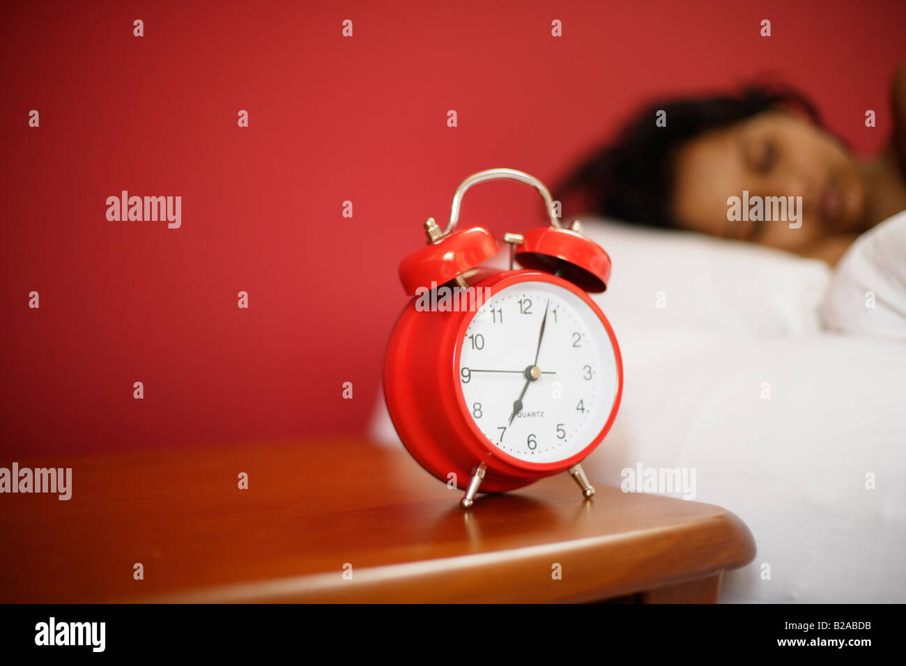 Indian woman 30s sleeps beside alarm clock - Stock Image