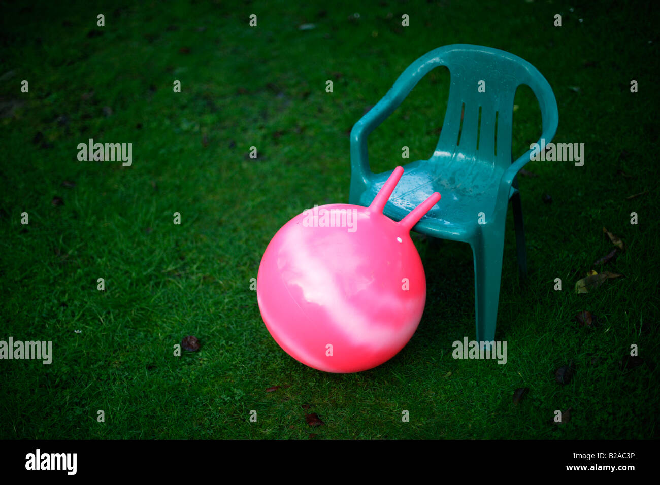 Pink moonhooper on green grass garden lawn with plastic chair - Stock Image