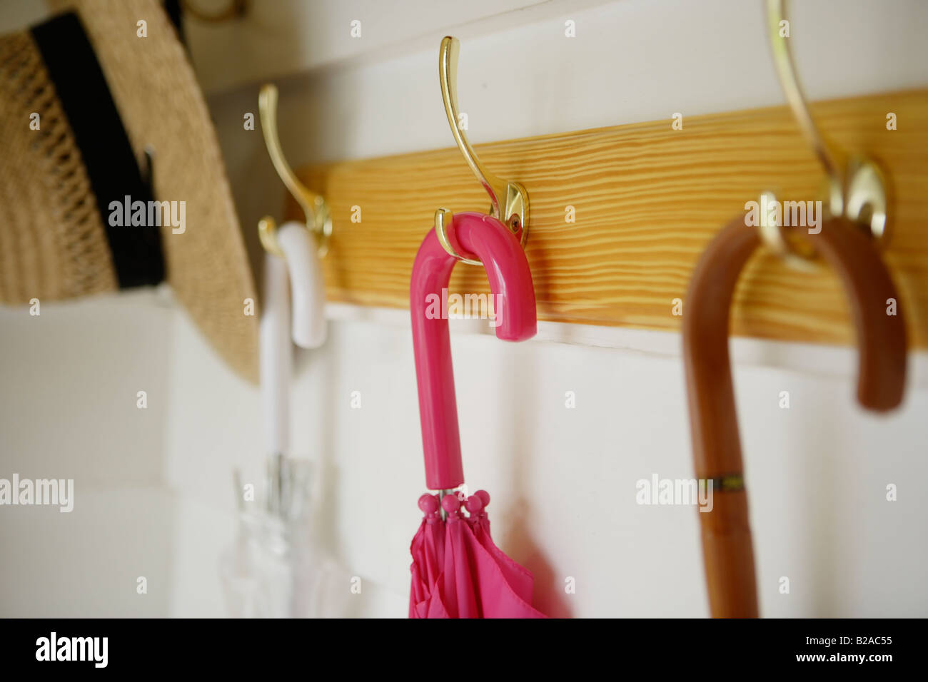 Umbrellas and straw hat hanging from coat rack - Stock Image