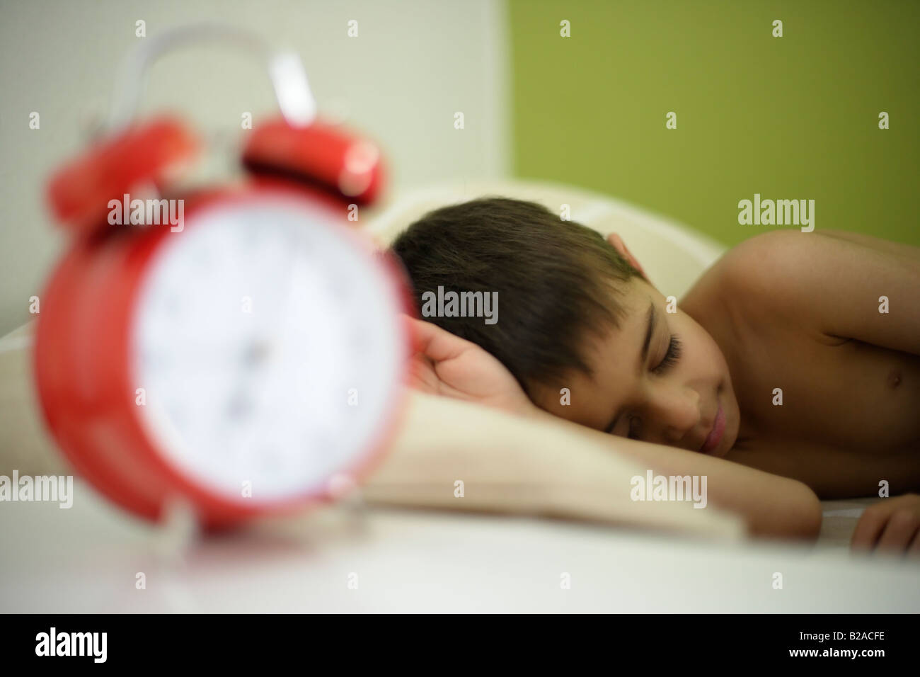 Boy aged six sleeps in his bed beside bright red alarm clock Mixed race indian english - Stock Image