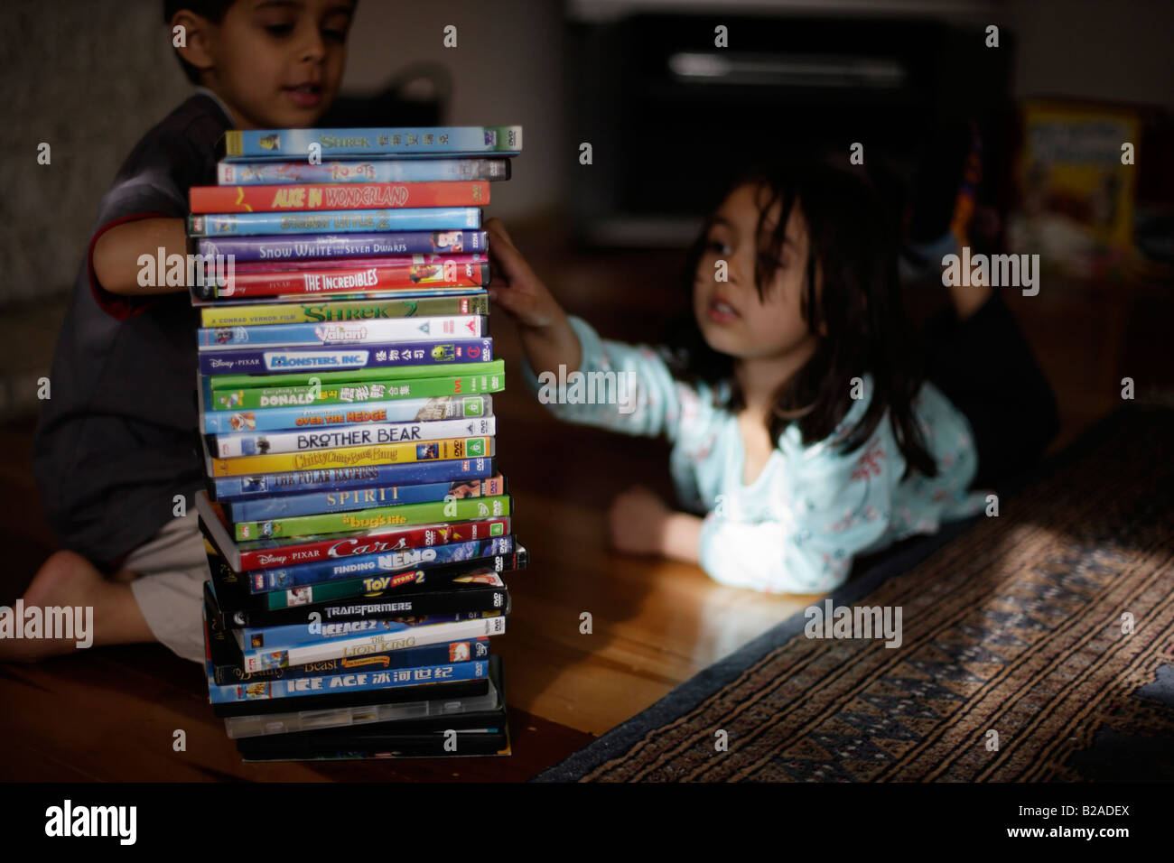 Brother aged six and sister five consider their DVD collection Mixed race indian ethnic and caucasian - Stock Image
