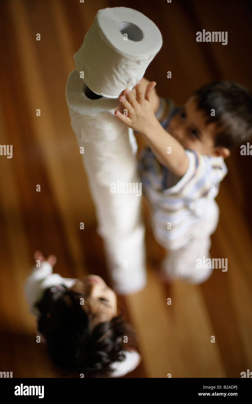 Children build tower of toilet rolls Boy aged six and sister five Mixed race indian ethnic and caucasian - Stock Image