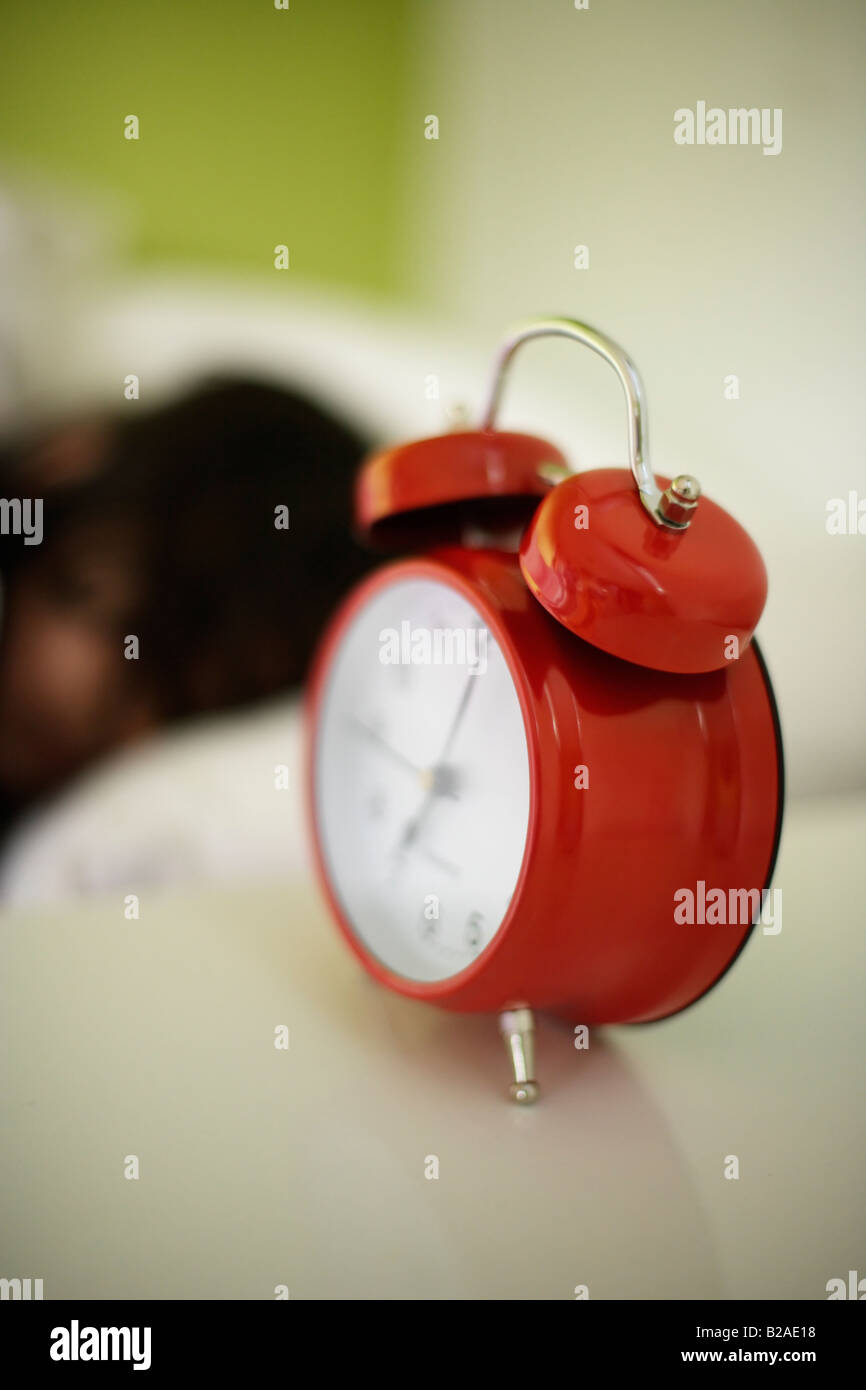Girl aged five sleeps in her bed beside bright red alarm clock Mixed race indian english - Stock Image