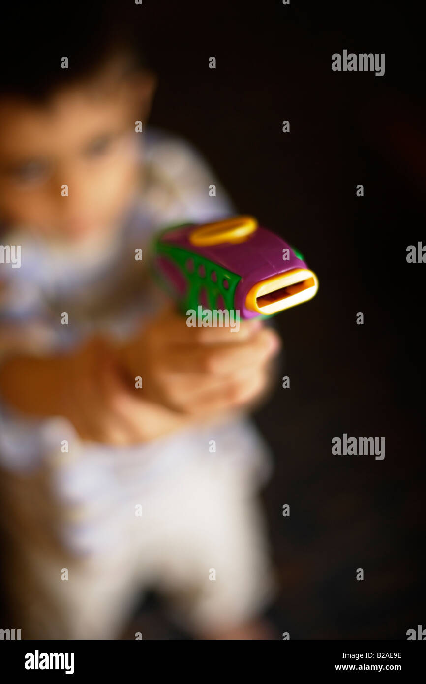 Boy takes aim with toy pistol Six year old mixed race indian ethnic and caucasian - Stock Image