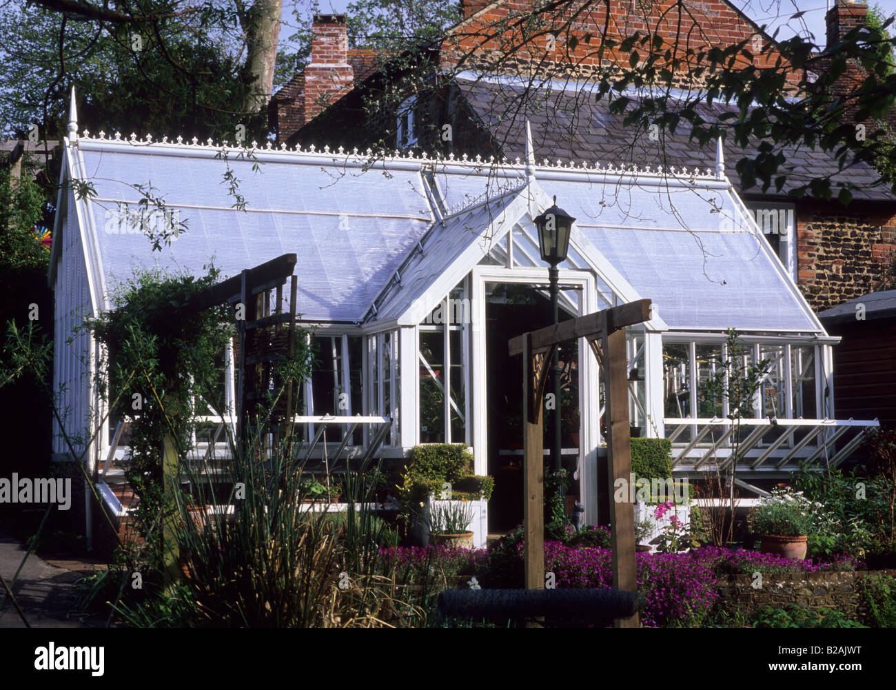 Tilford Cottage Surrey Alitex glasshouse with yew topiary chairs - Stock Image