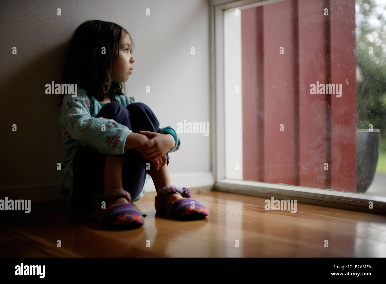 Portrait of little girl aged five sat on floor beside window Mixed race indian ethnic and caucasian - Stock Image