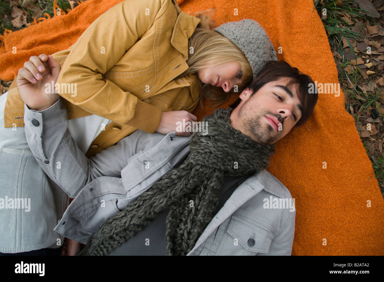 Young couple relaxing on blanket in park - Stock Image